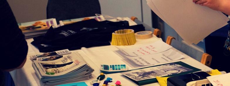 Kuvassa on pöytä, jolla on erilaisia papereita ja lehtiä.